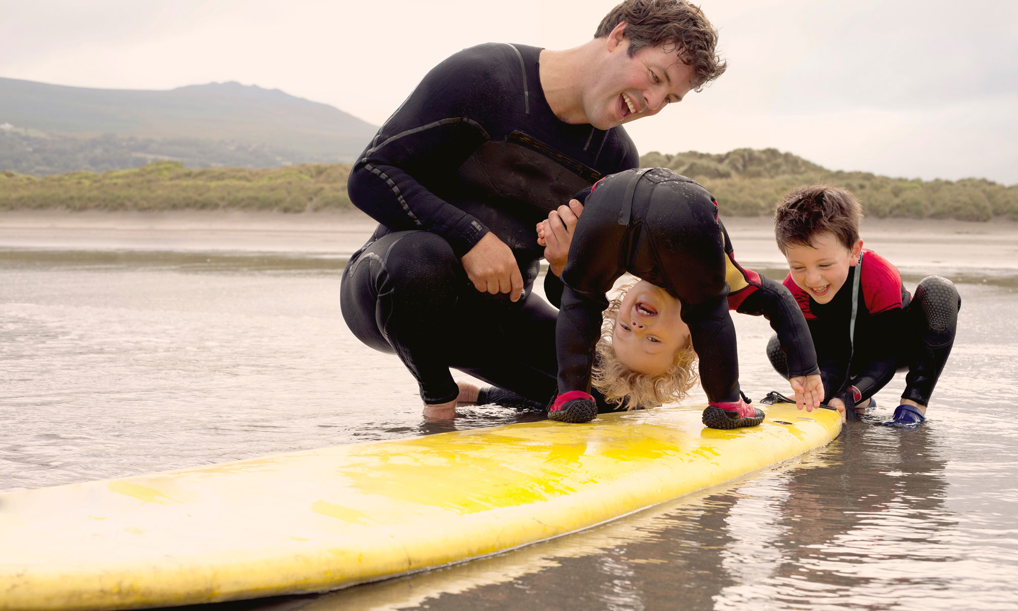 Dad with two sons playing with surfboard in the water.